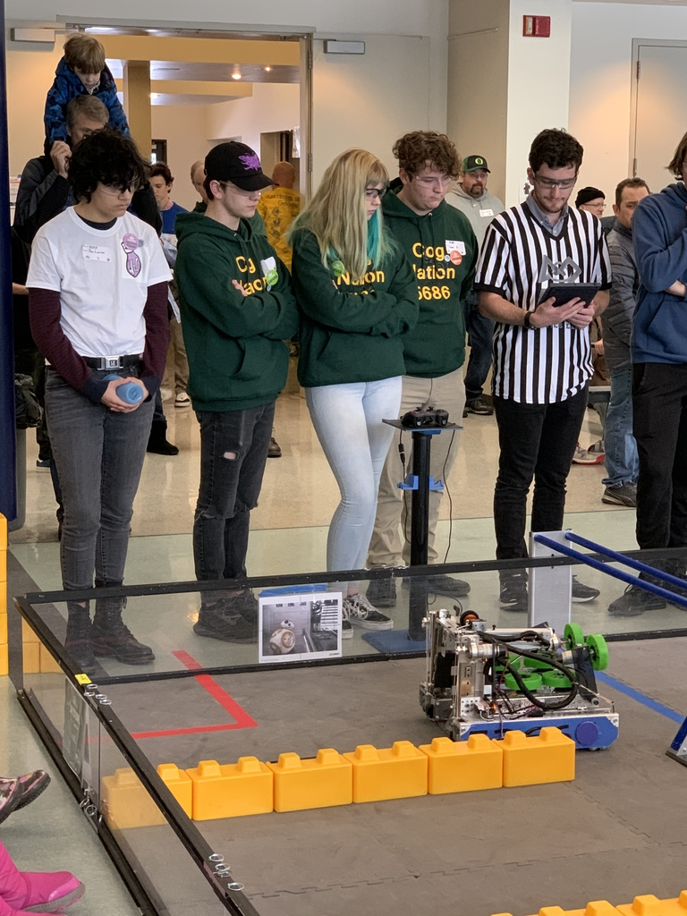 Steven, Grace, and Connor watch as their robot completes the autonomous stage of thee match